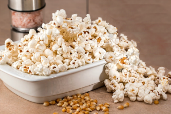 Popcorn spilling out of a white serving bowl.
