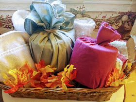 2 Toilet paper rolls wrapped in fabric in basket of towels, fall leaves